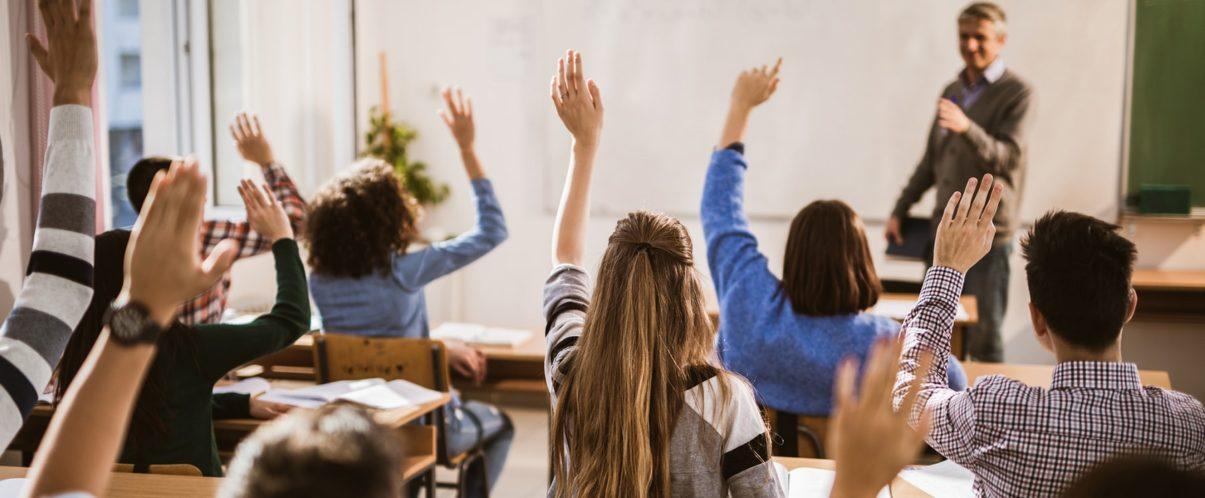 nursing students raising hands in classroom